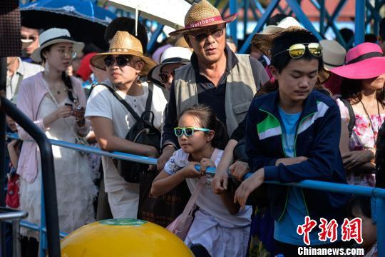 图为游客排队乘船。